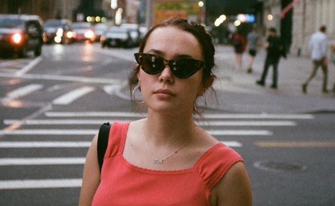 Lucy Loken wearing a pink top with cat-eyed glasses.
