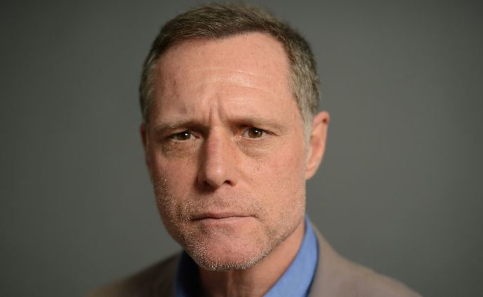Jason Beghe on a grey suit and blue shirt.