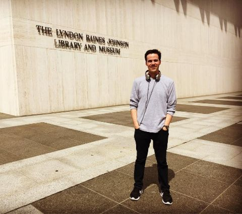 Robert Costa standing in front of The Lyndon Baines Johnson Library and Museum.
