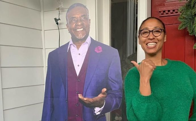 Dionne Lea Williams standing next to her husband Keith David's poster.