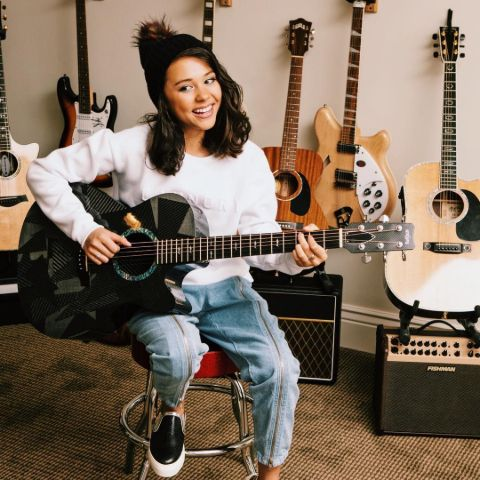 Breanna Yde playing a guitar.