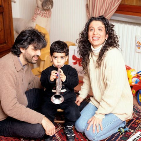 The Italian tenor Andrea Bocelli in his house in Tuscany with his wife Enrica Cenzatti and their two years old son Amos, all seated on an eastern carpet in the playroom of the child; in october Andrea and Enrica had their second baby, named Matteo. Forte dei Marmi (LU), Italy, 1997.