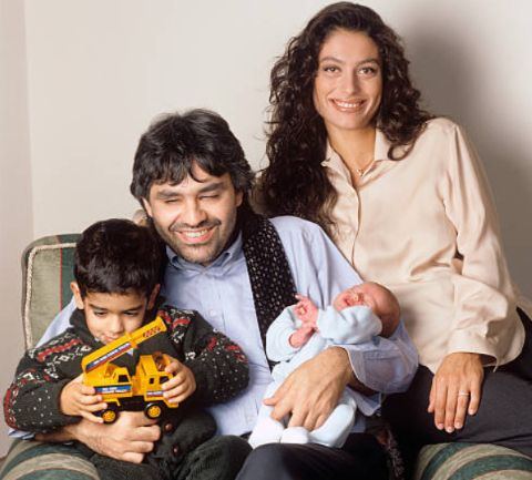 The Italian tenor Andrea Bocelli sits on an armchair holding his two children, alongside with his wife Enrica Cenzatti: the two years Amos, on the left, who's playing with a toy crane, and Matteo, on the right, who's just born. Forte dei Marmi (LU), Italy, 1997.