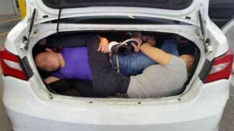 Chinese Immigrants stacked under the car trunk.