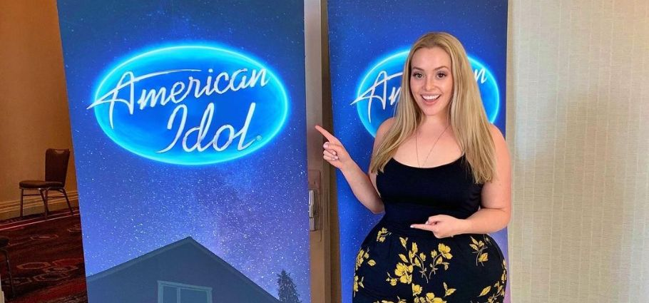 Grace Kinstler pointing towards American Idol banner.