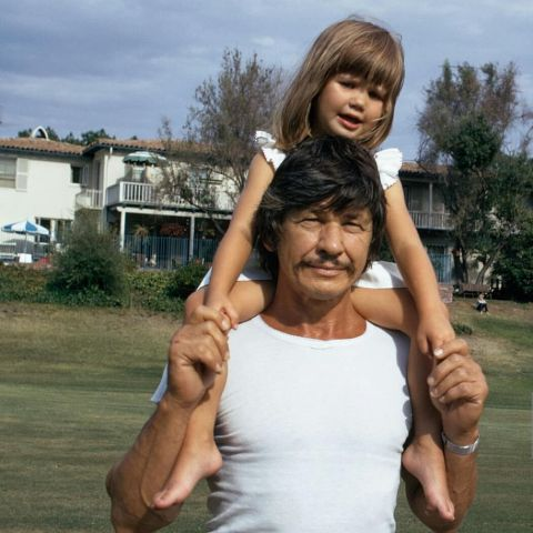 An old photo of Charles Bronson carrying his daughter Zuleika Bronson on his back.