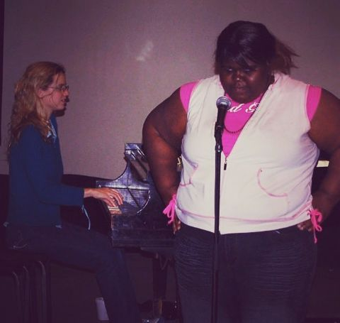 Gabourey Sidibe during her 20s ready to sing on stage.